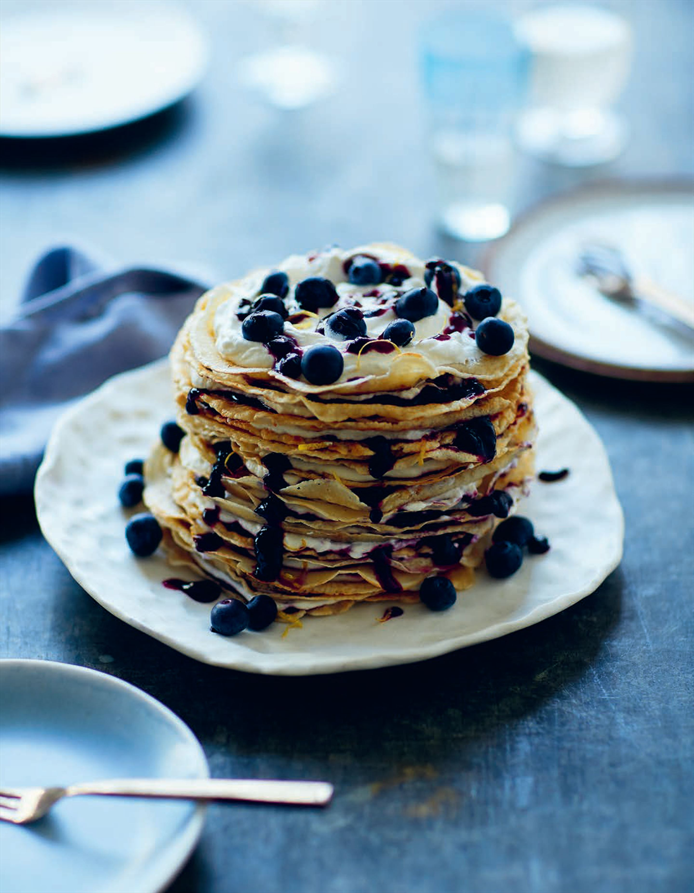 Celebration pancake cake layered with cream & blueberry compote