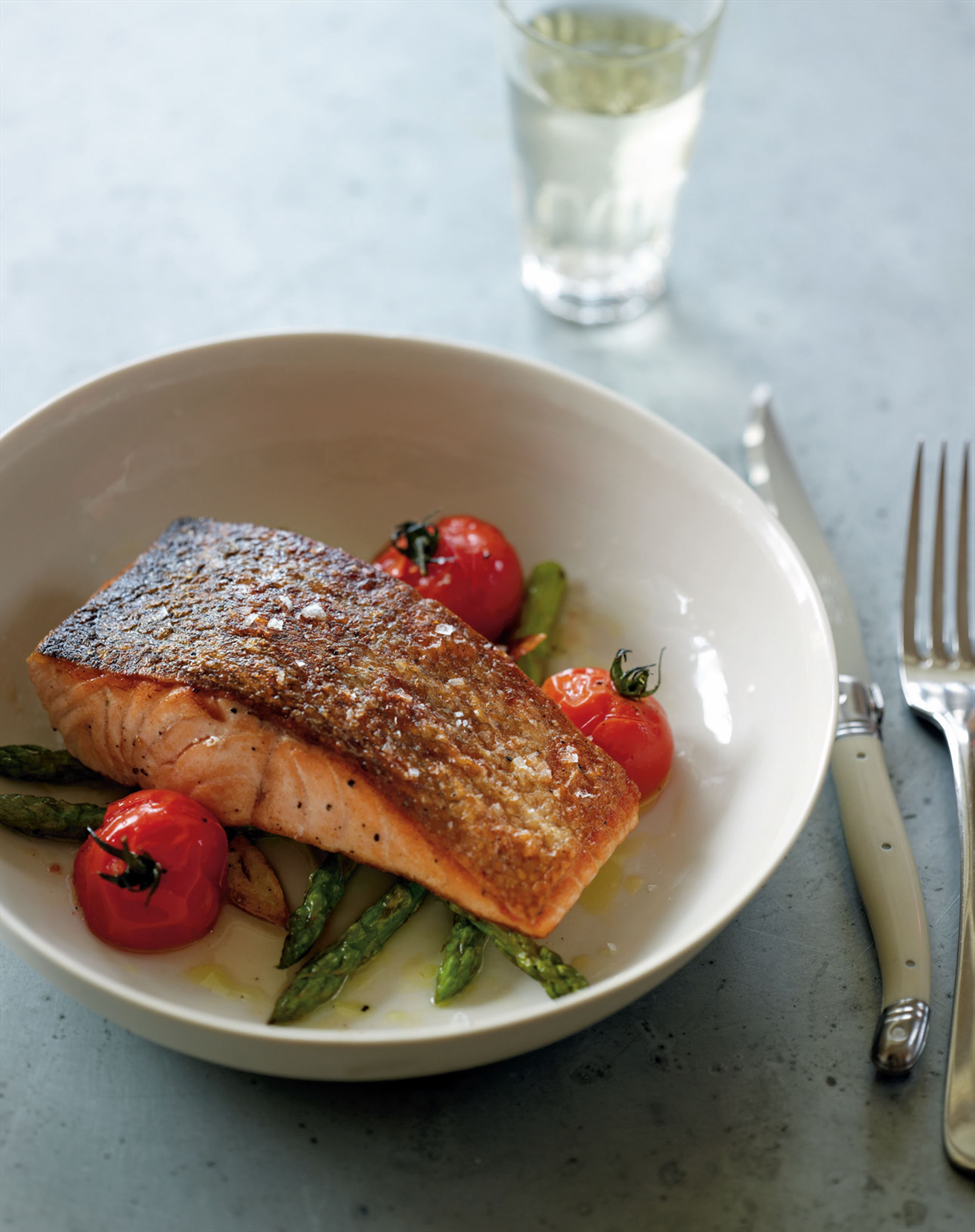 Crispy-skinned salmon with roasted asparagus and baby tomatoes