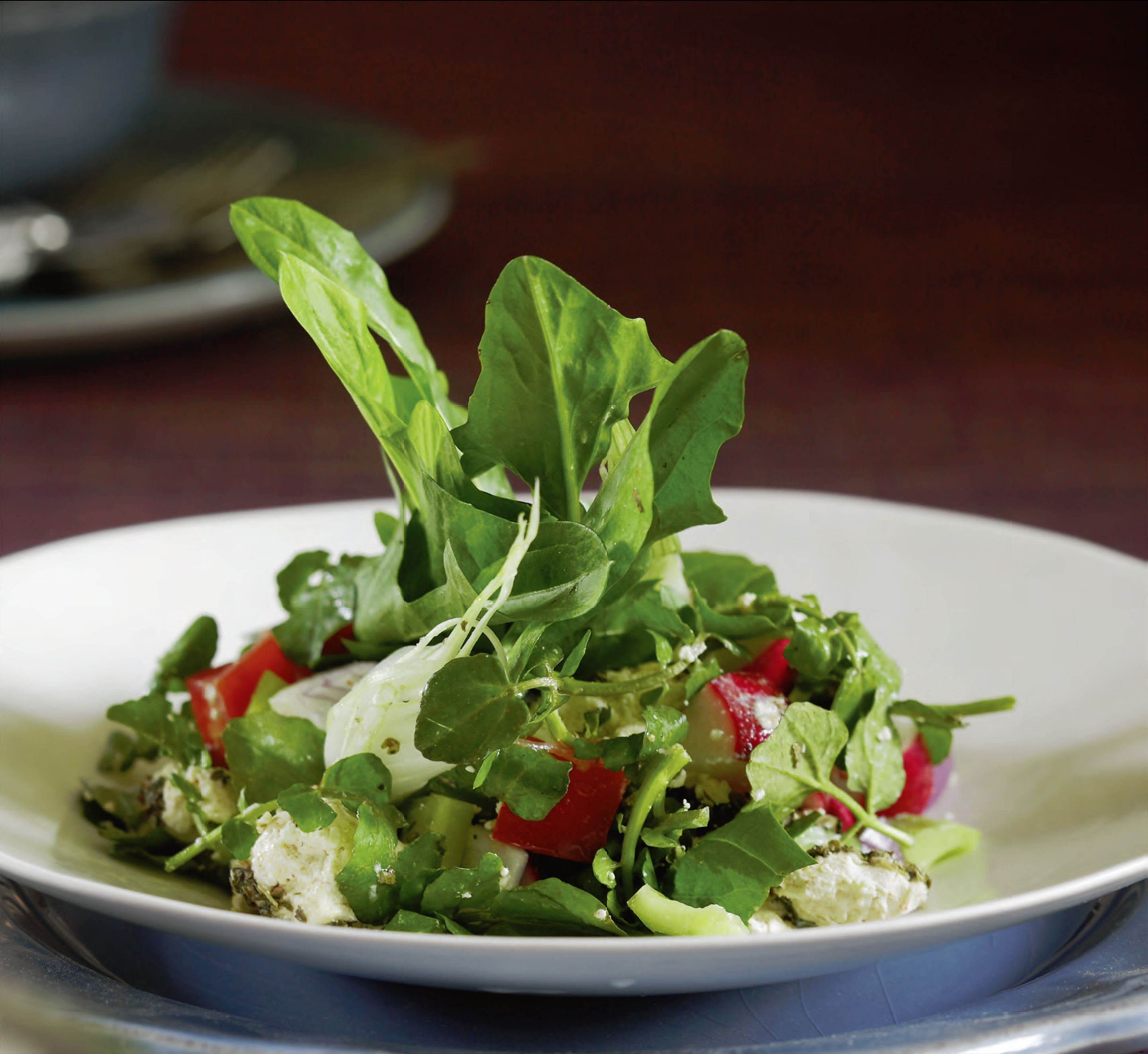 Soft herb salad with goat's cheese, crisp bread, sumac and pine nuts
