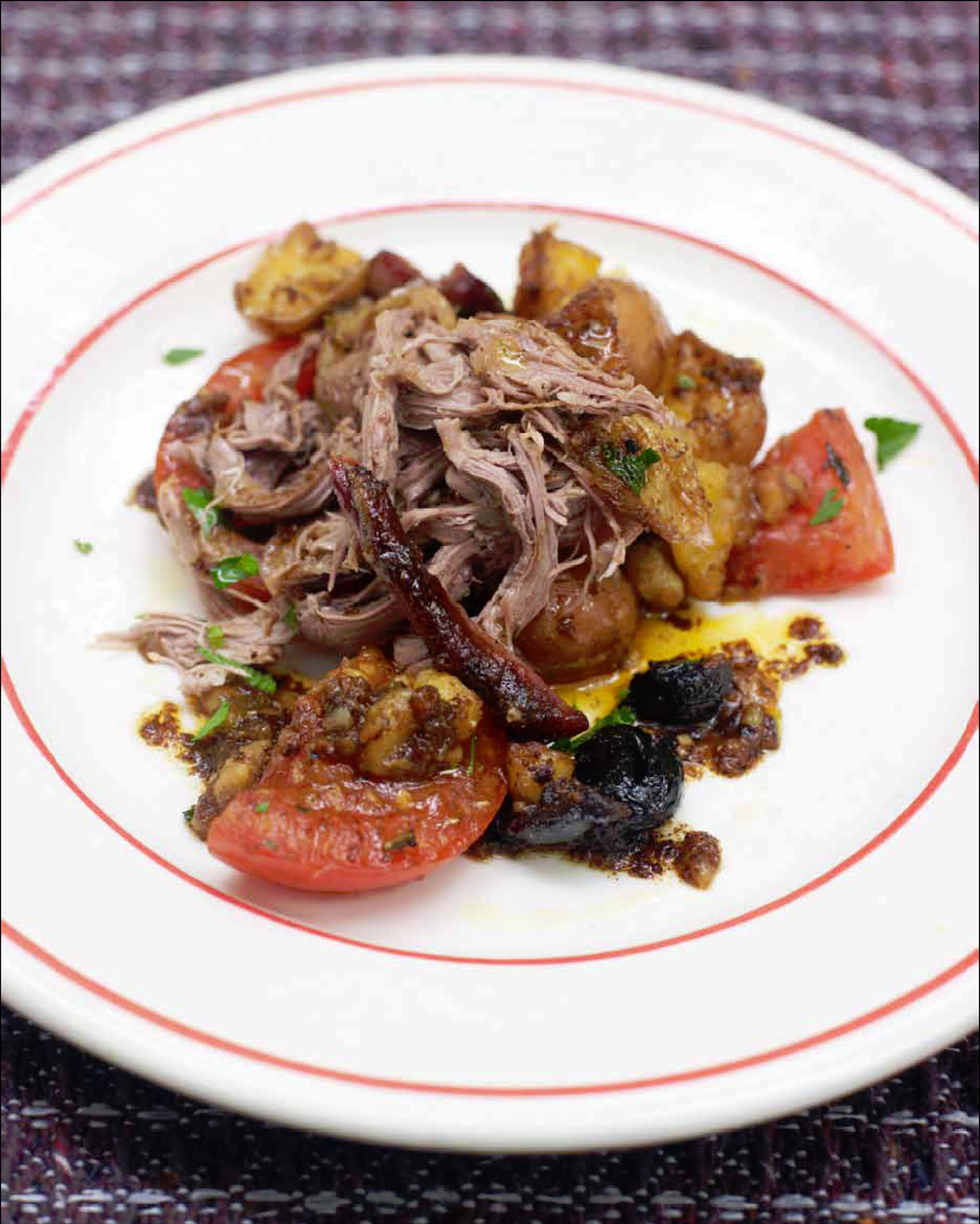 Mechoui lamb with crushed roast potatoes & tomatoes