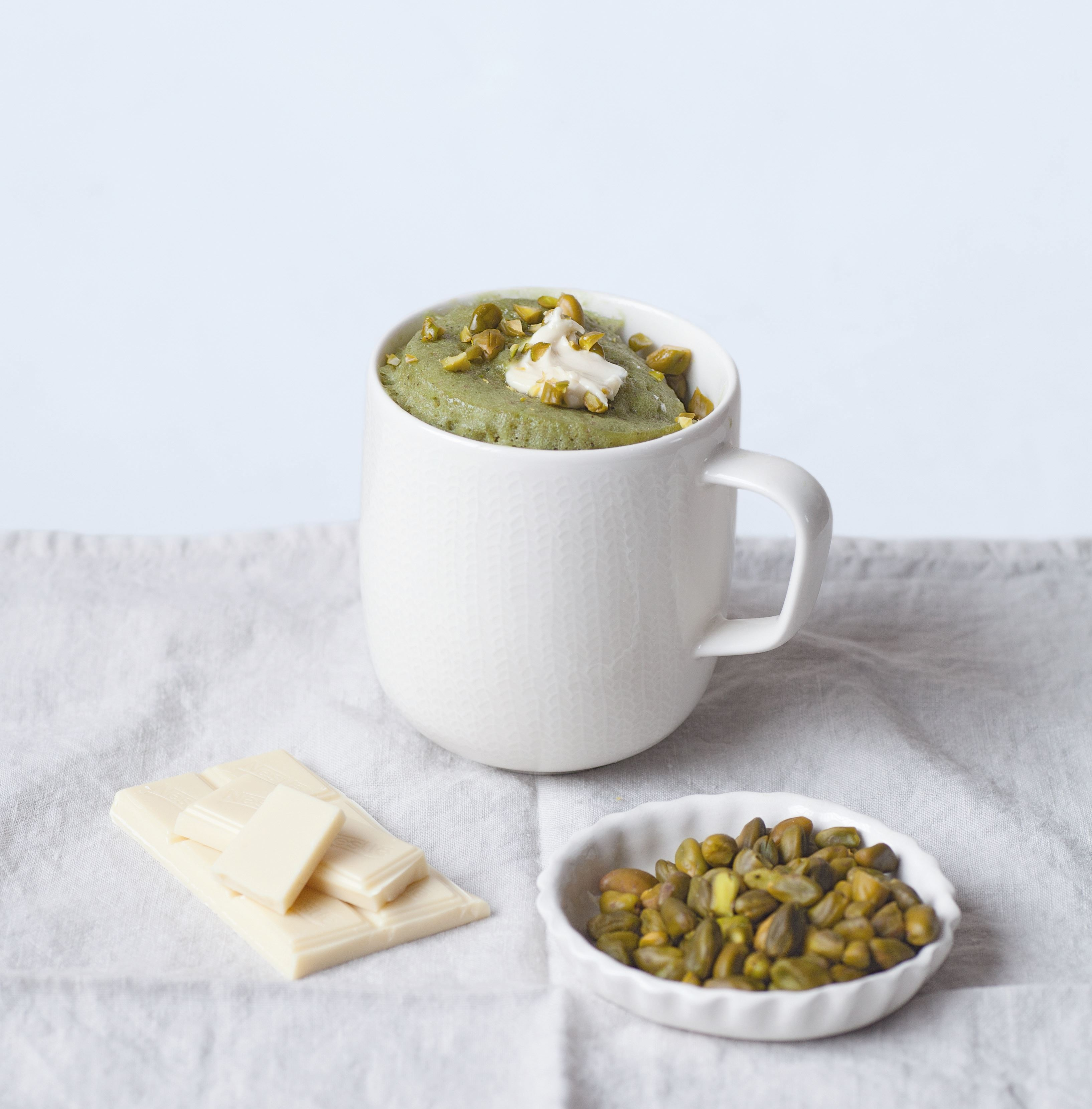 Pistachio mug cake with a white chocolate middle