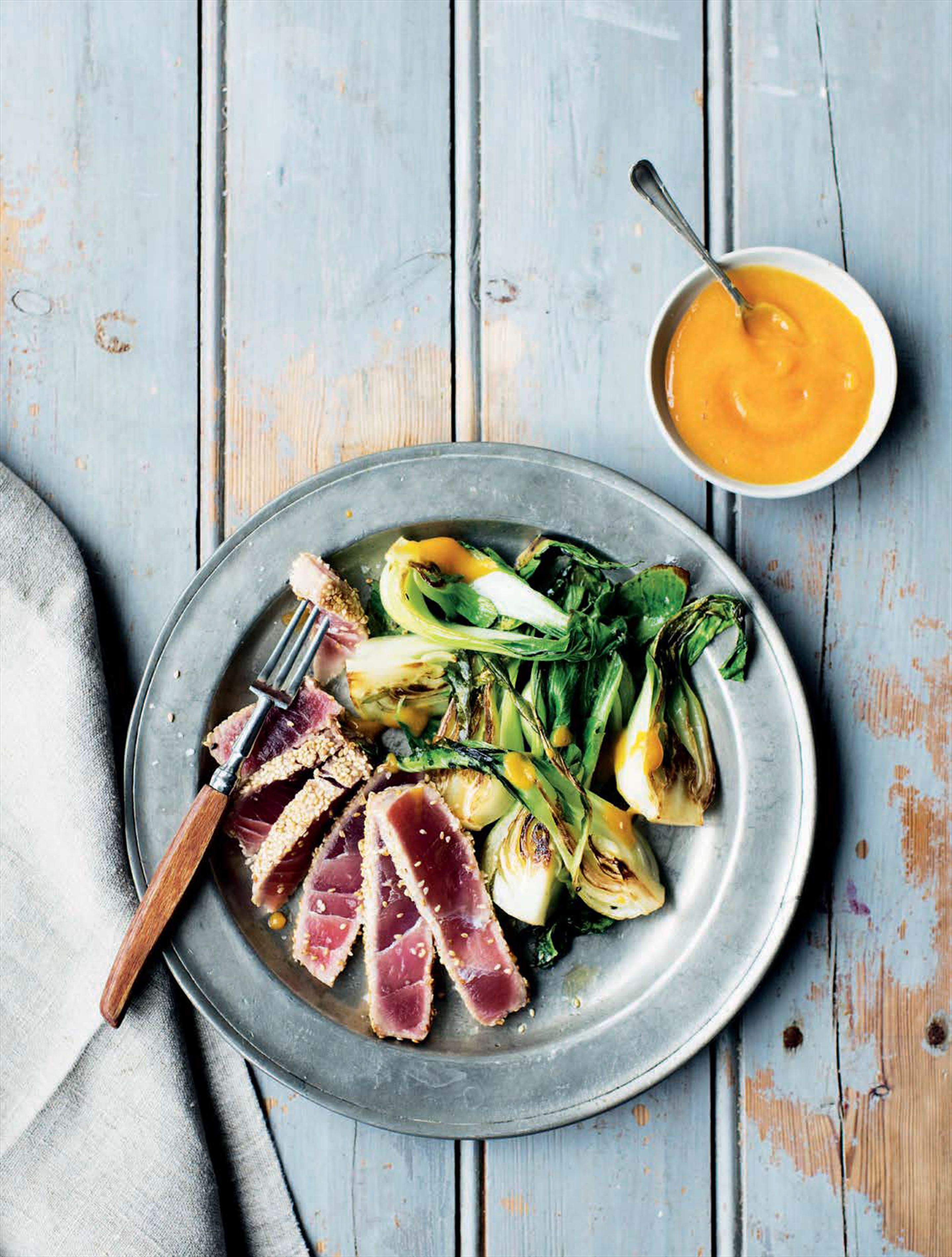 Sesame-crusted tuna with lime, mango and chilli coulis and wilted pak choi