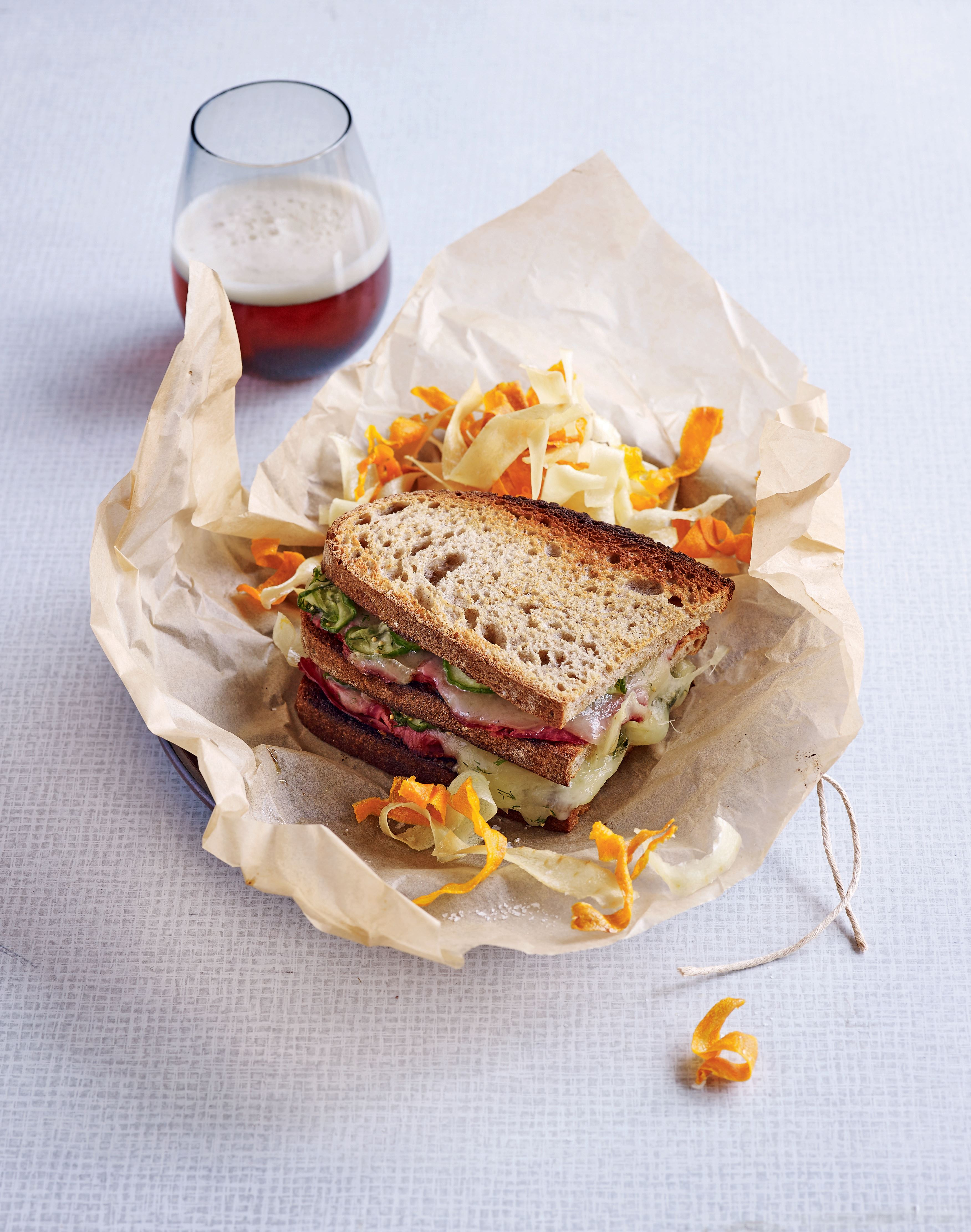 Hot paper bag pastrami, fontina and pickled cucumber sarnie with parsnip and carrot crisps