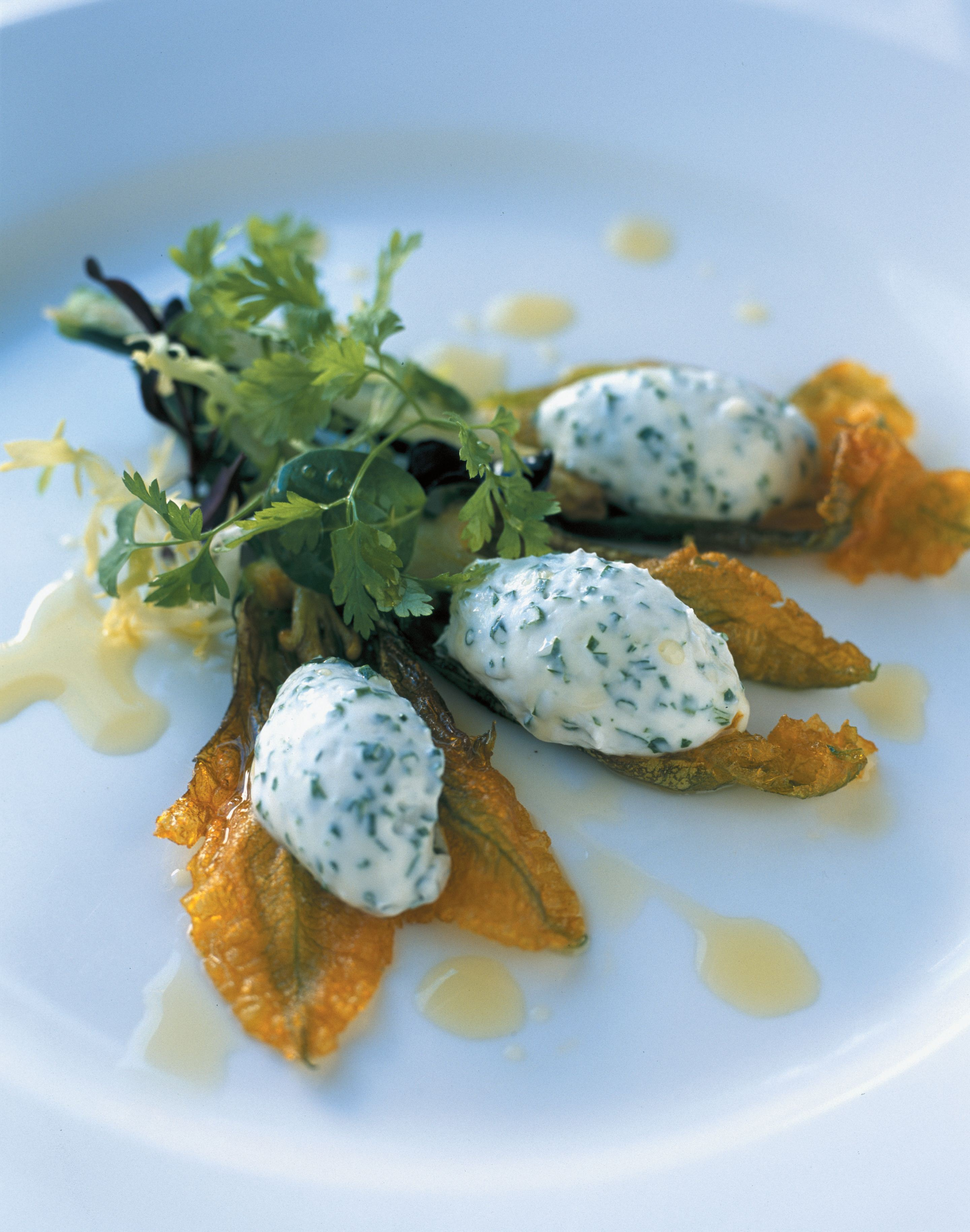 Deep-fried zucchini flowers with chive and shallot-whipped goat's curd and a herb salad
