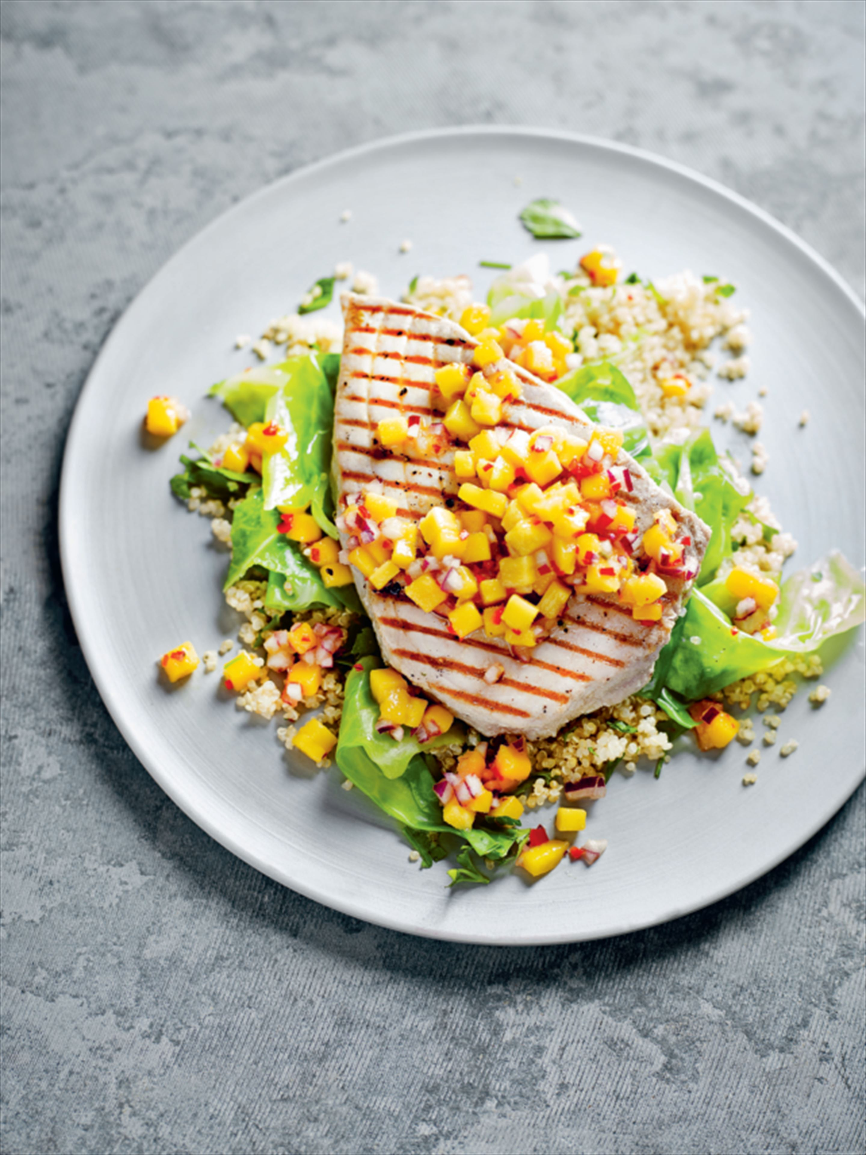 Tuna steak with mango salsa, wilted greens and quinoa verde