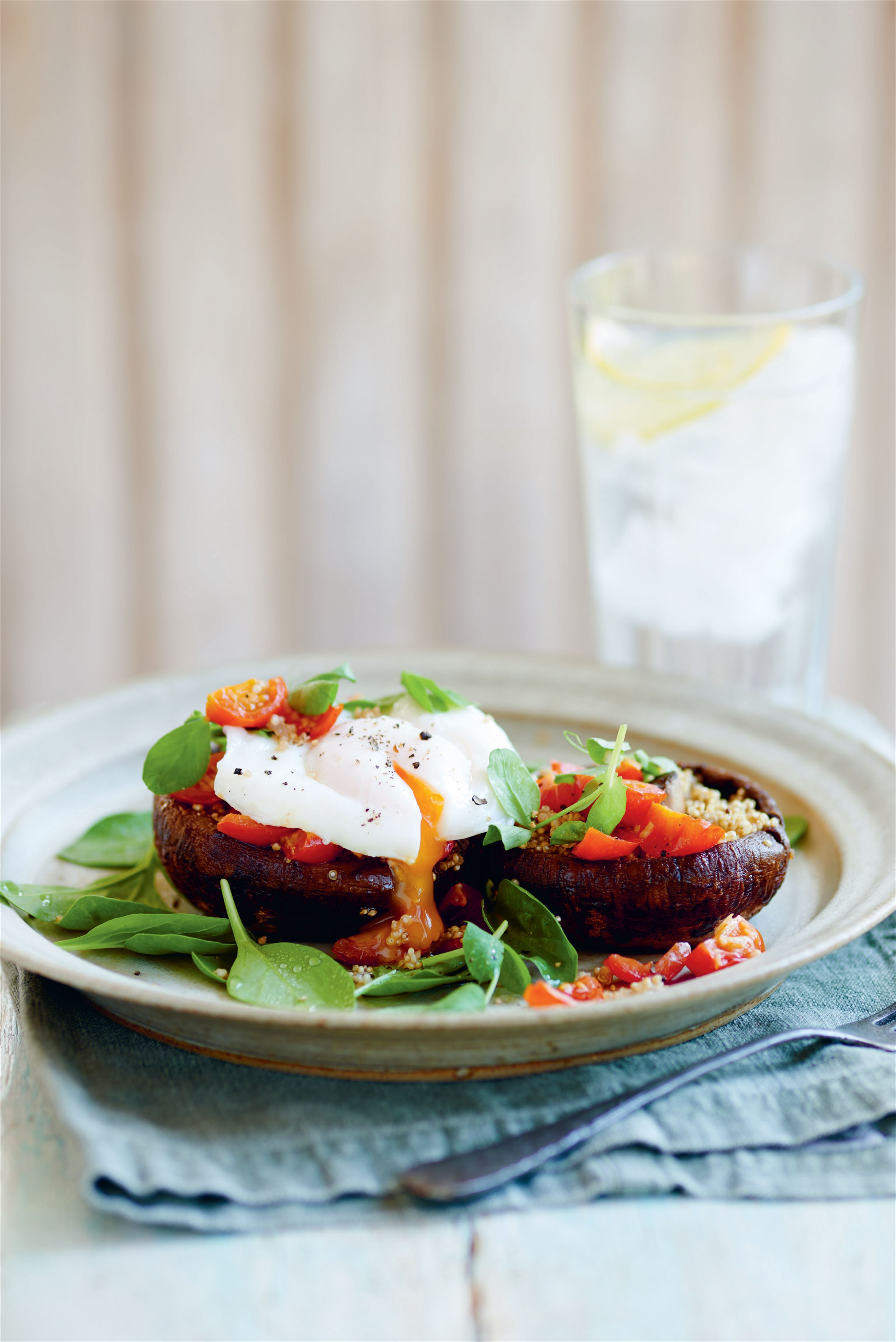 Quinoa-stuffed mushrooms with garlic tomatoes and poached egg