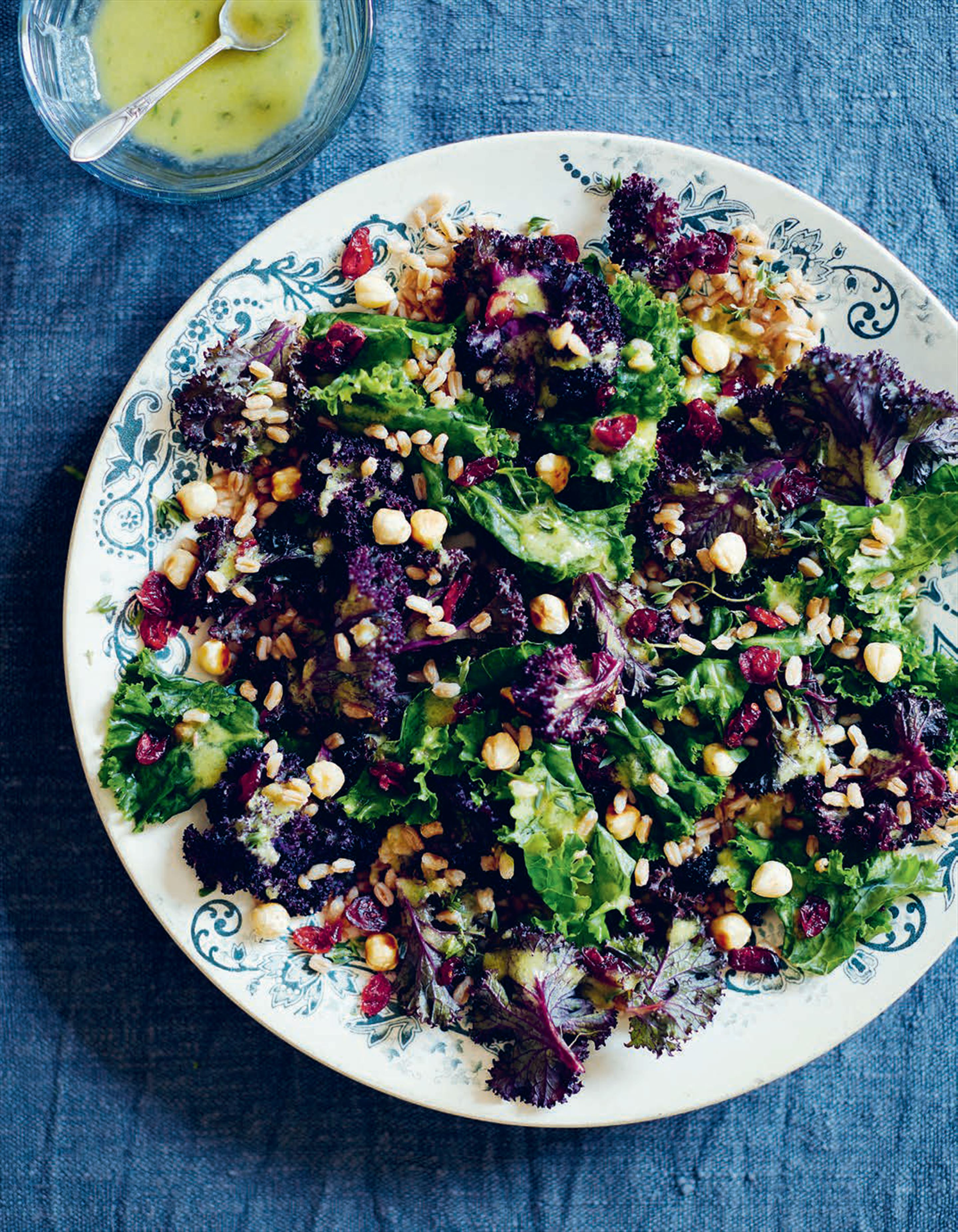 An autumn salad with massaged kale, spelt, dried cranberries, lime & hazelnuts