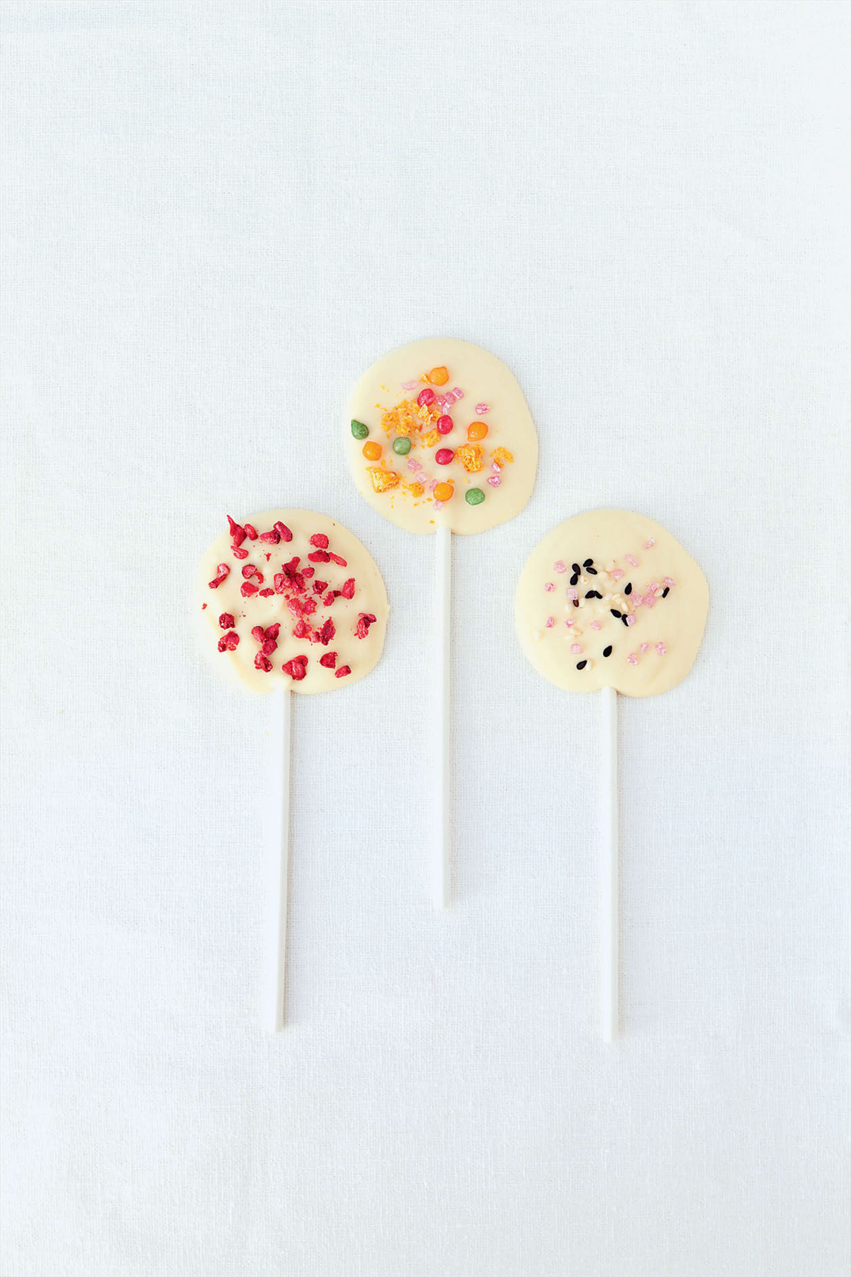 Chocolate lollipops with toppings and sprinkles