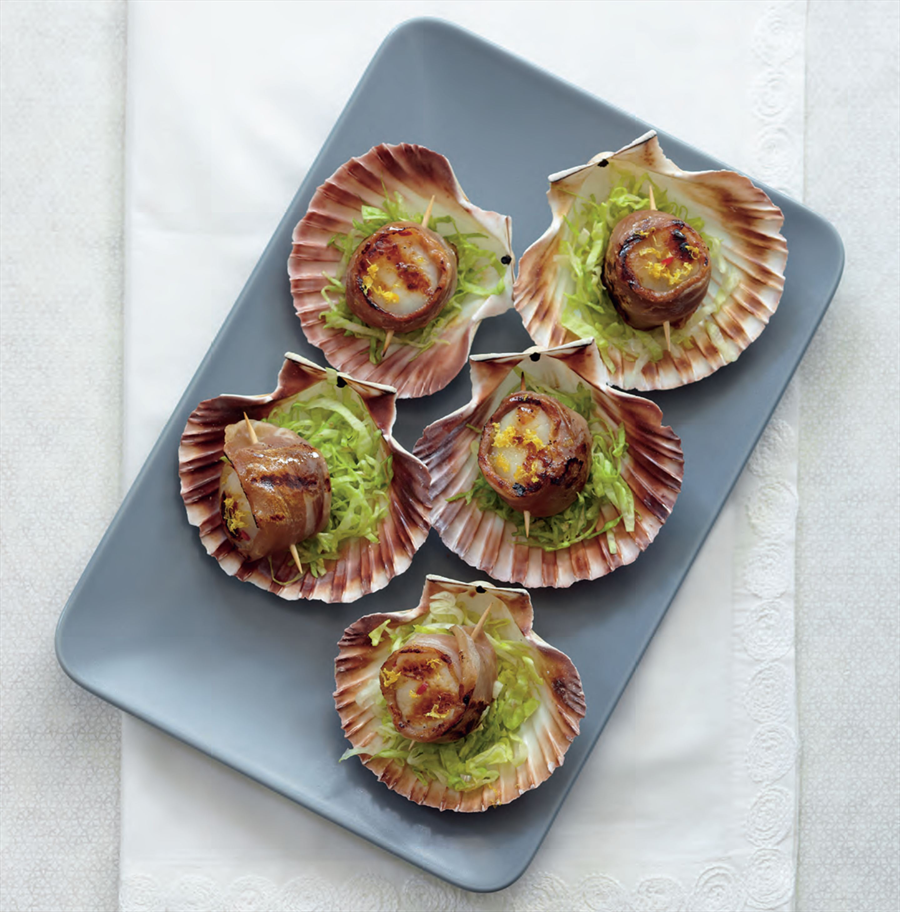 Char-grilled scallops wrapped in prosciutto