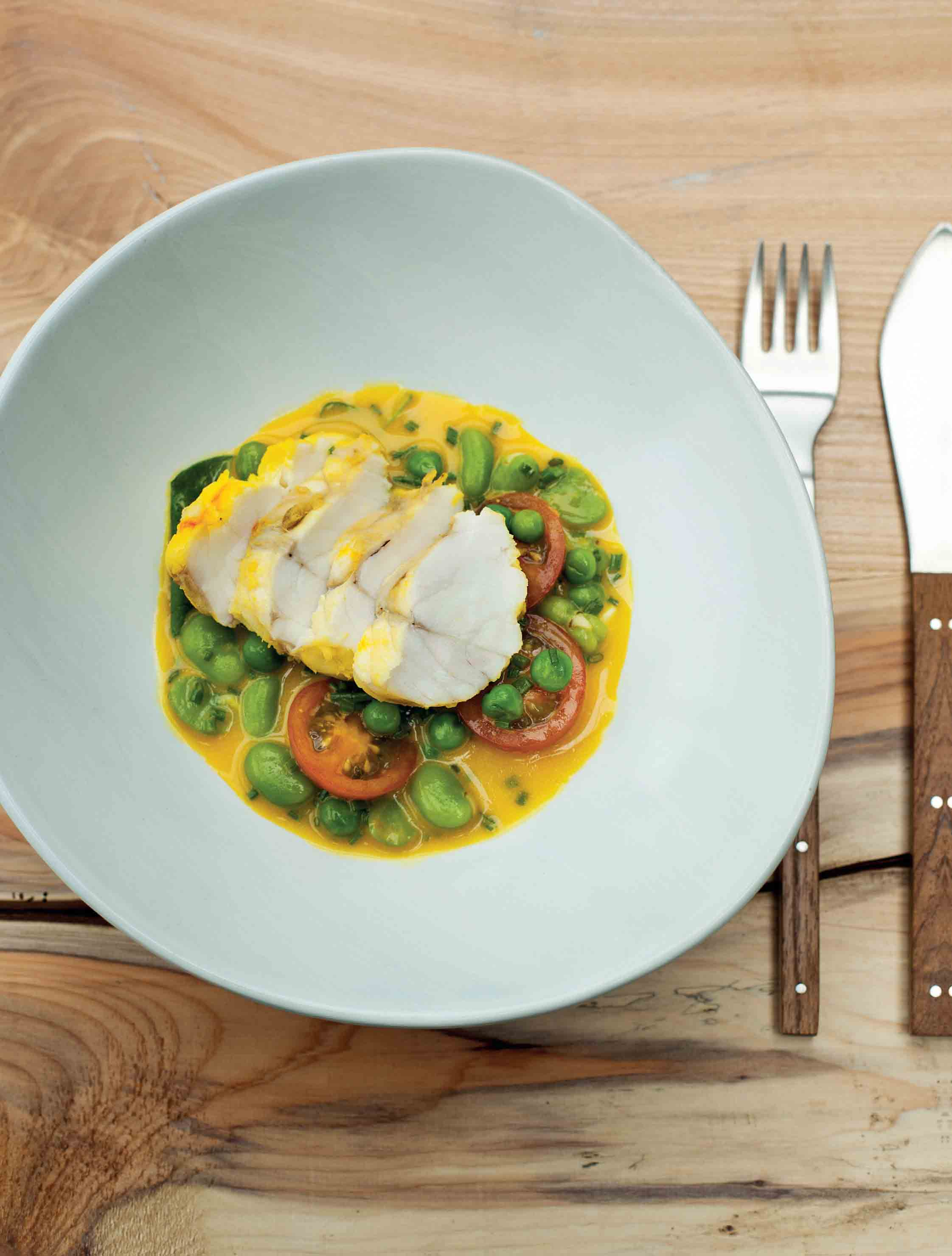 Monkfish poached in a saffron broth with peas and broad beans