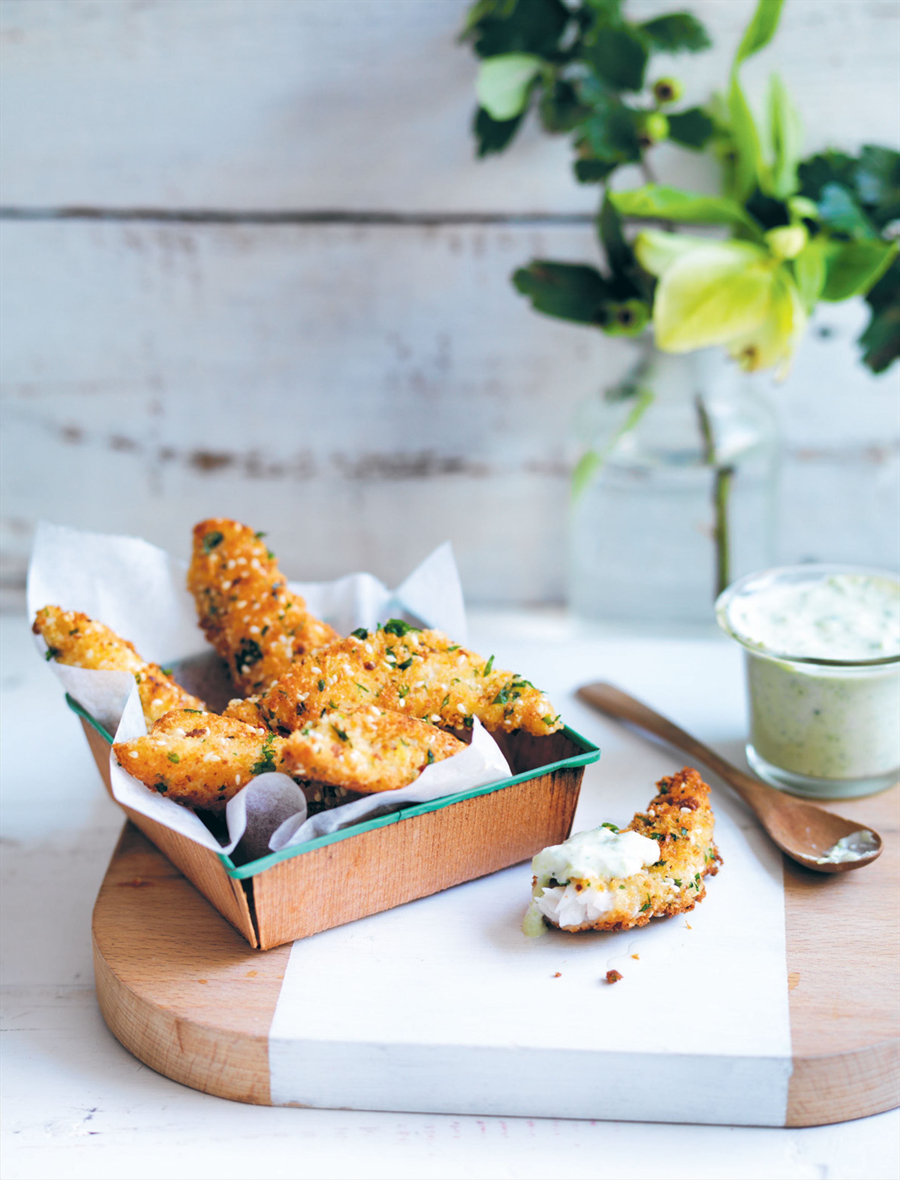 Sesame-crunch fish fingers with broad bean yoghurt sauce