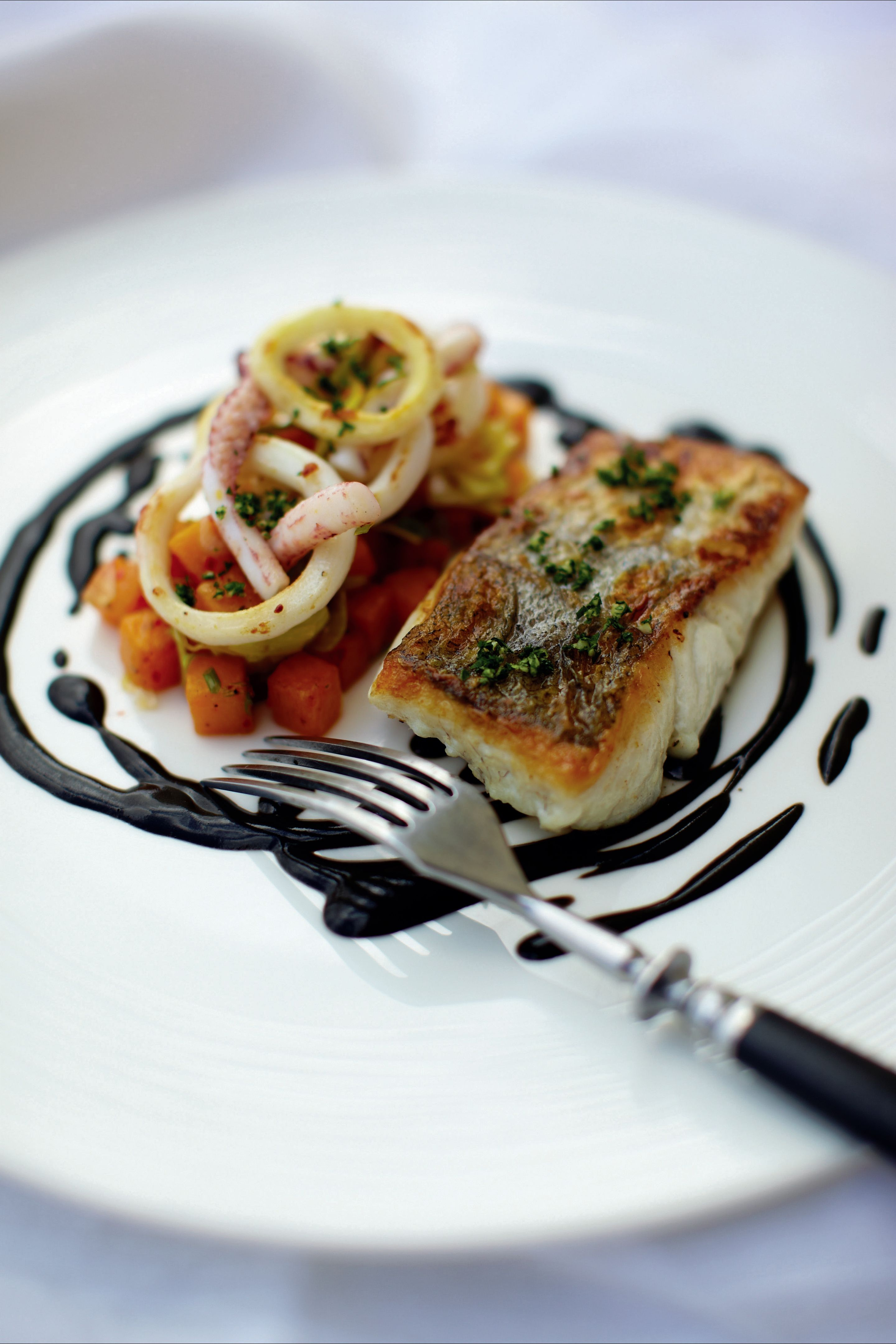 Salt hake with squid ink, parsley and tomato and garlic sauce