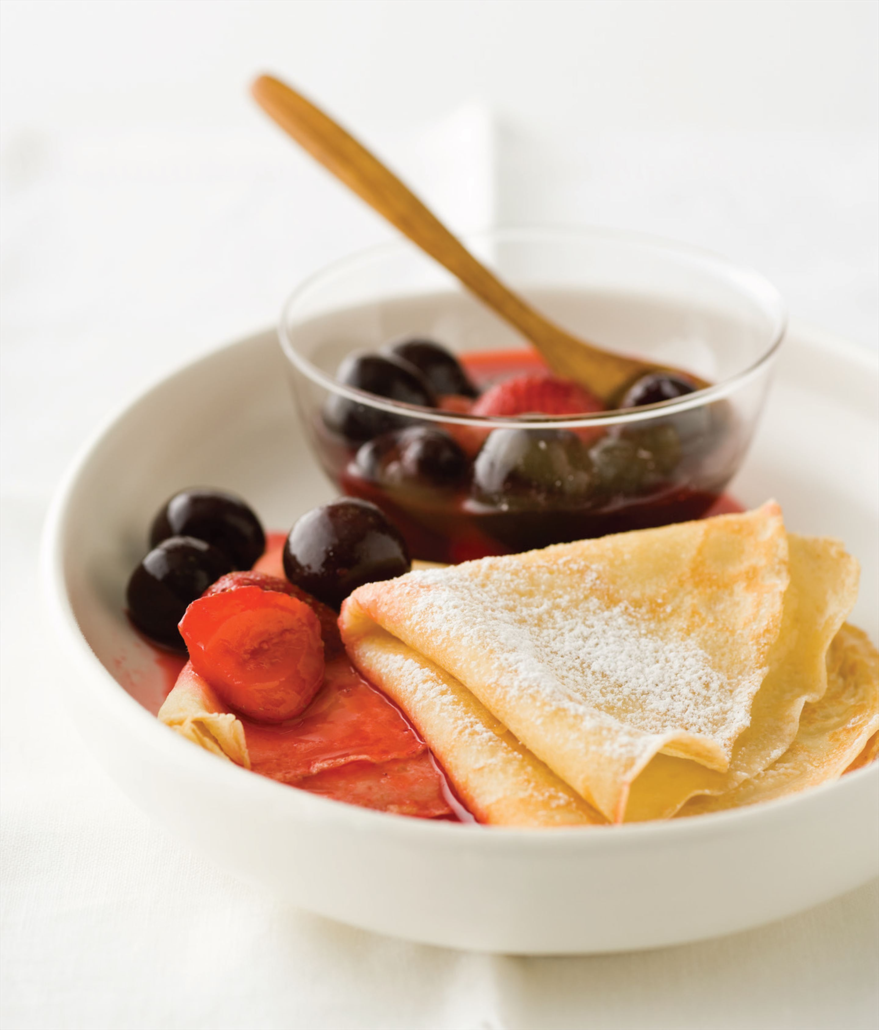 French crêpes with poached cherries and berries