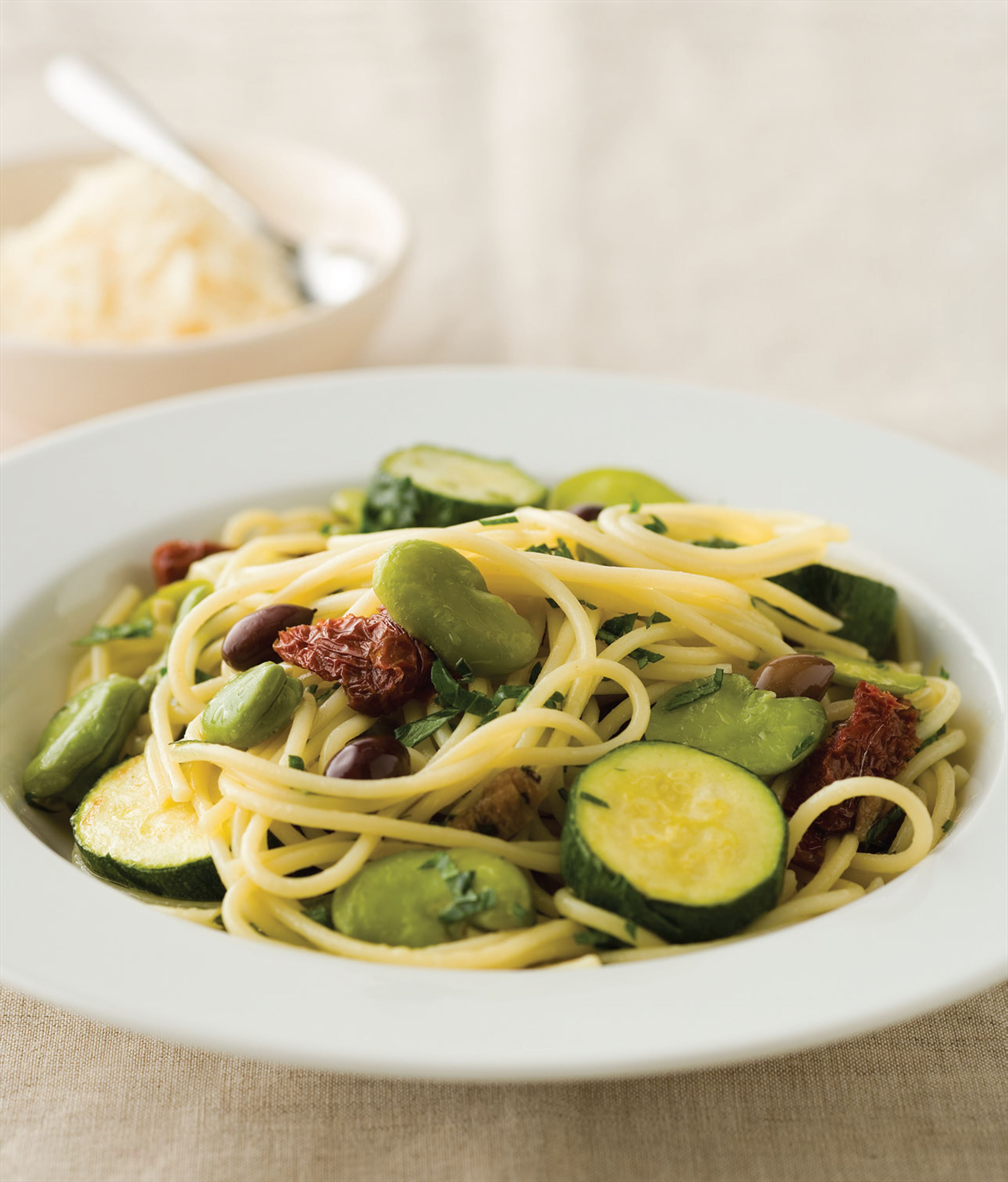 Spaghetti with zucchini, broad beans and olives