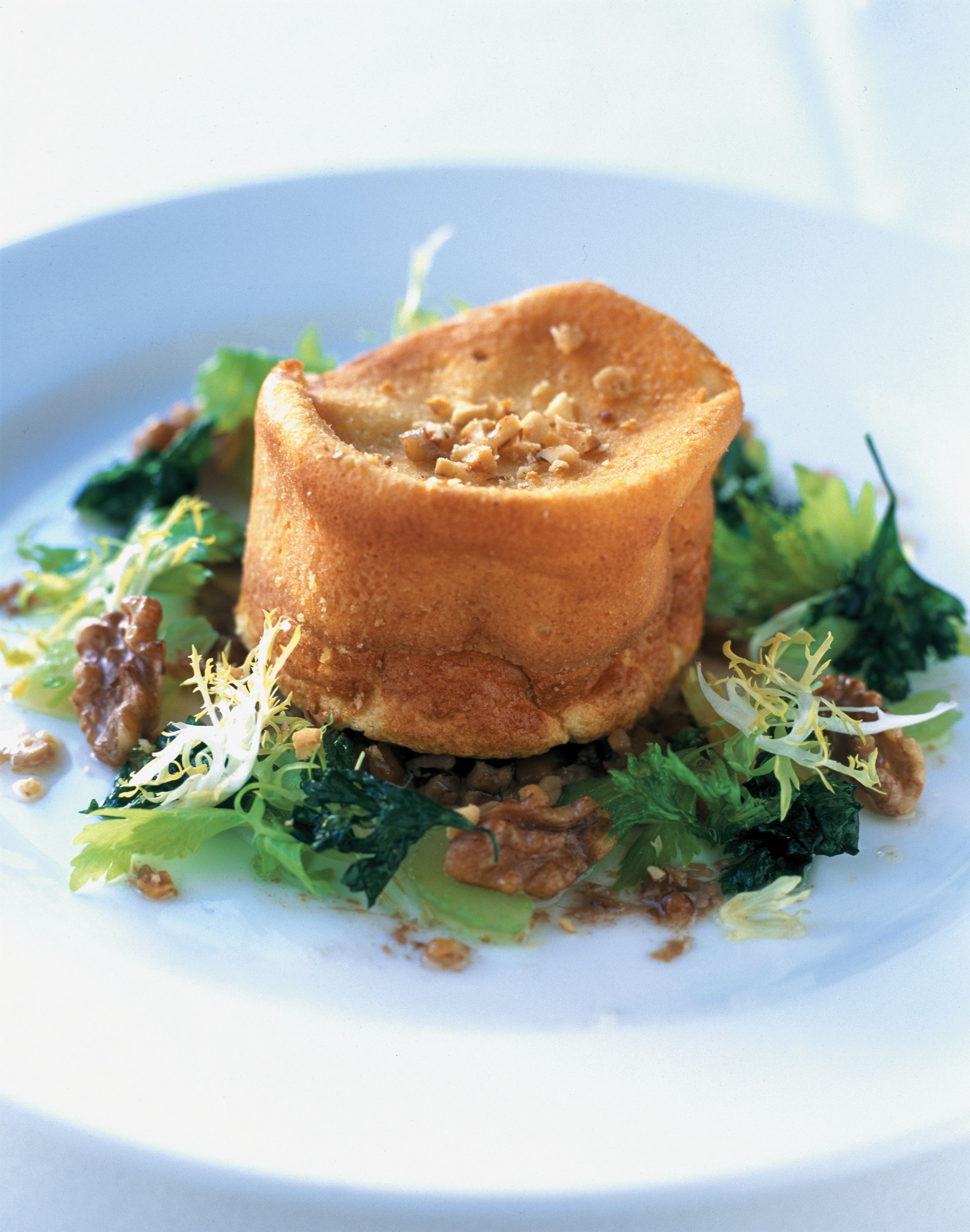 Double-baked cabecou soufflé with a celery leaf and frisée salad and walnut vinaigrette