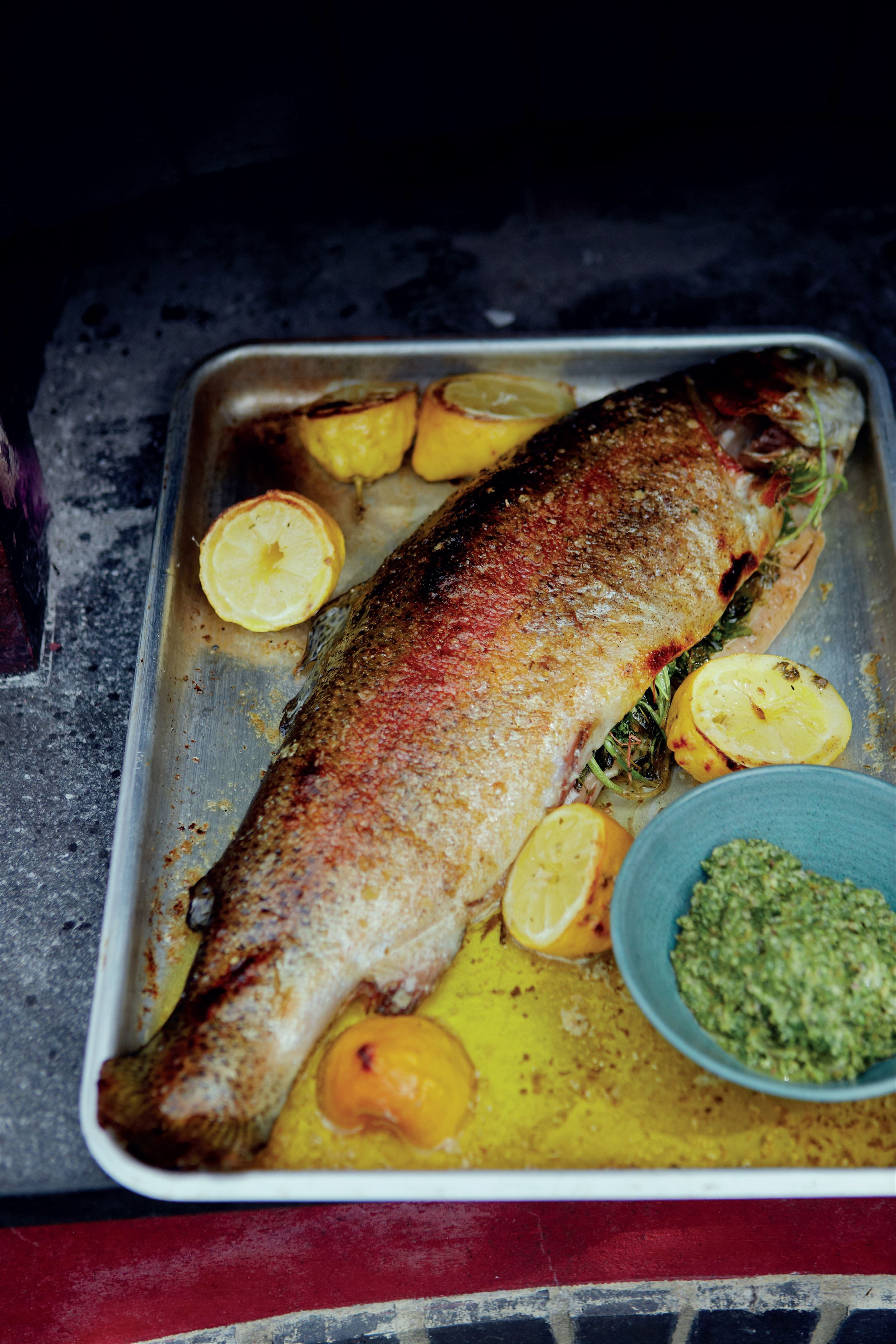 Whole roast trout with salsa verde, roast lemons and new potatoes