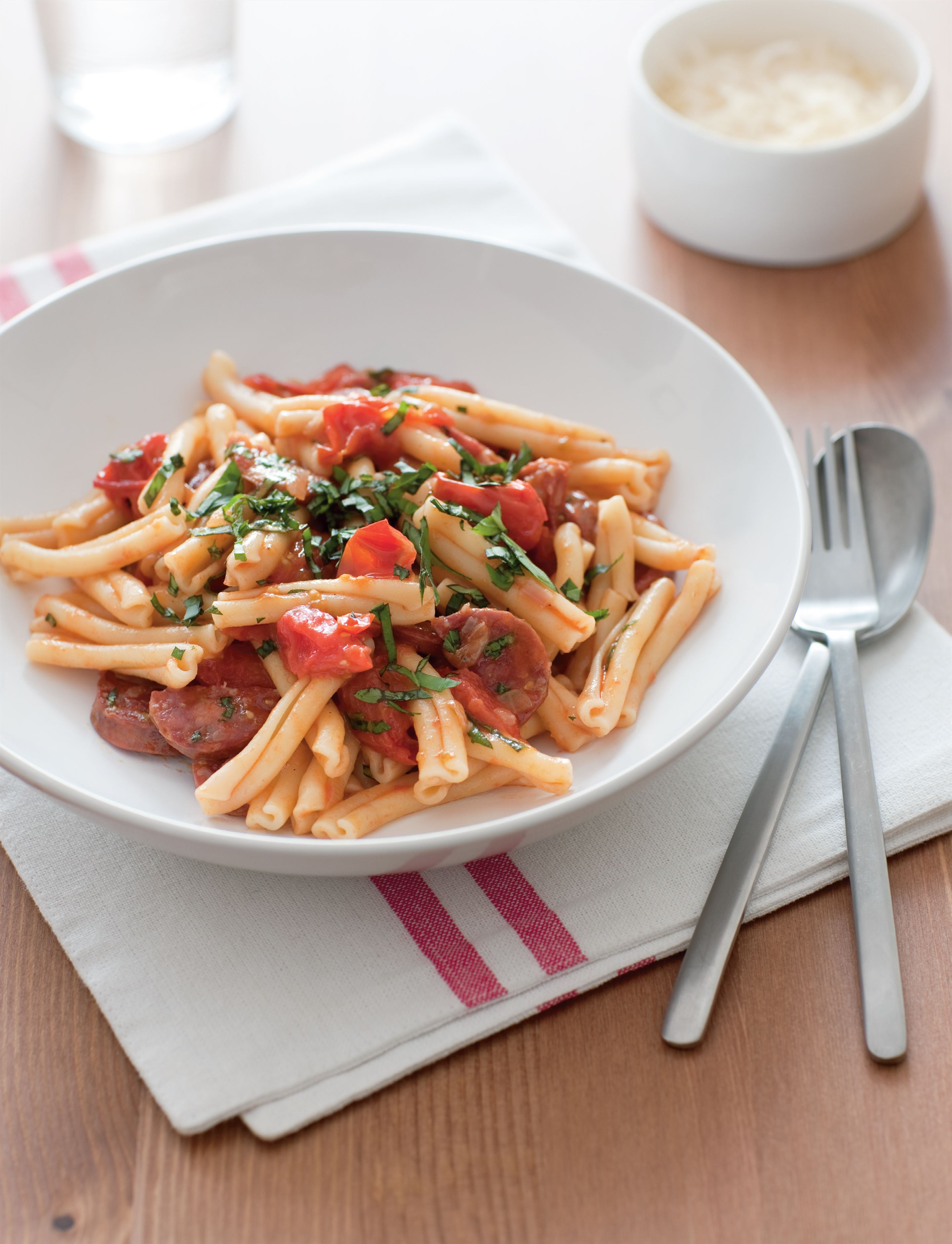 Pasta with cherry tomatoes, spicy salami and basil