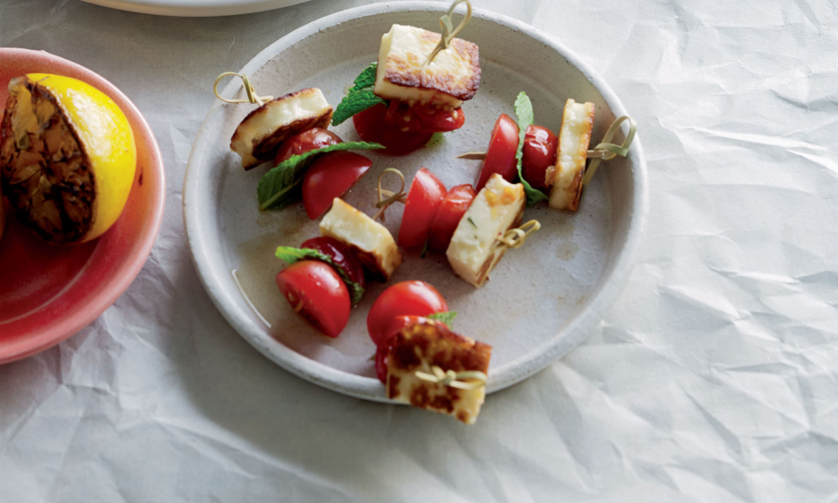 Roasted and fresh tomato skewers with mint and halloumi