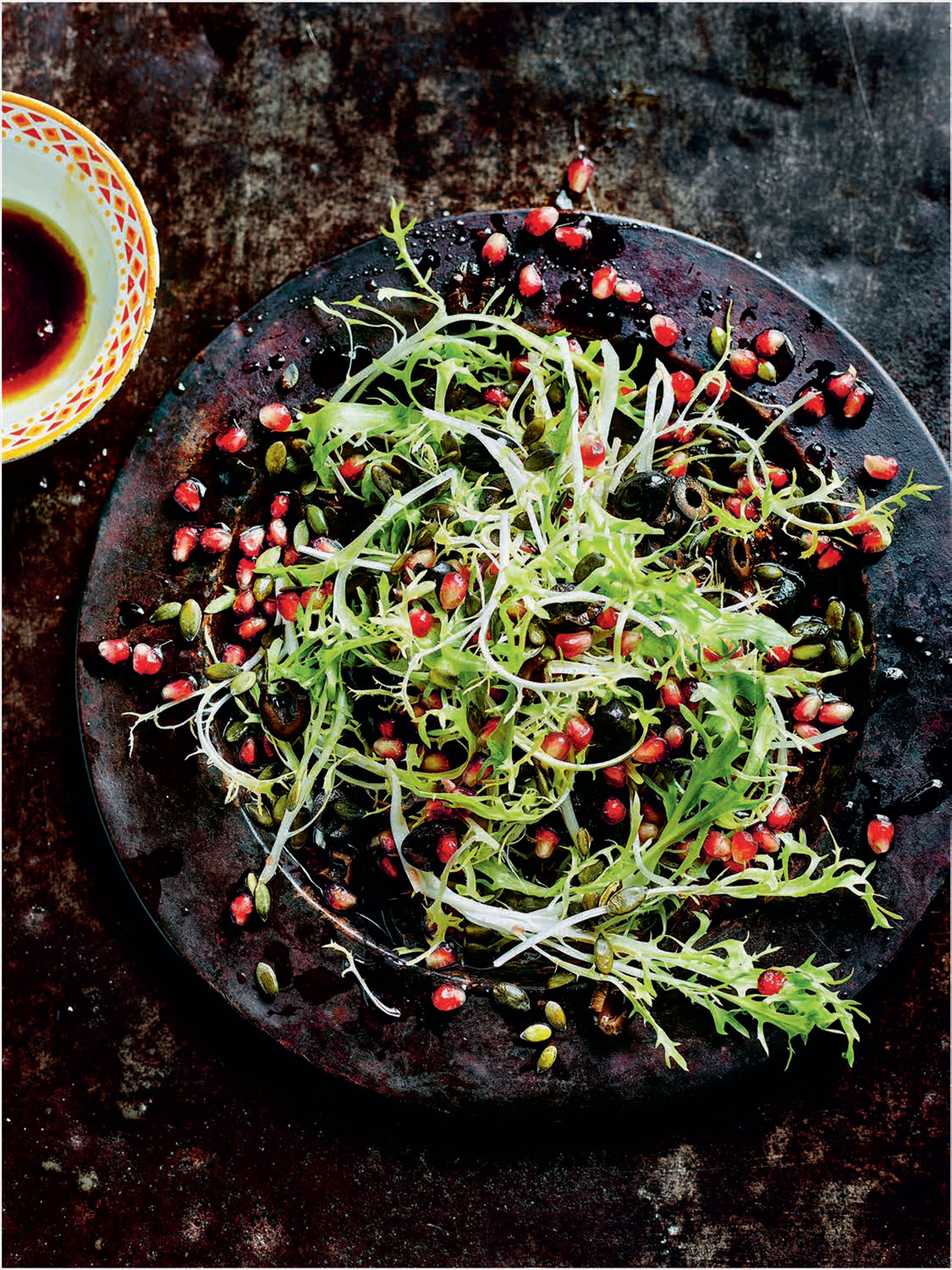 Frisee lettuce, pomegranate and olive salad